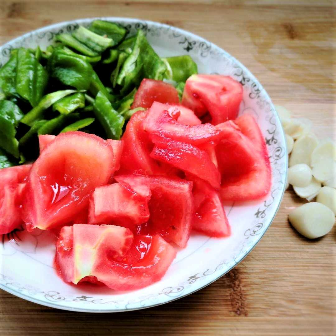 Tomatoes are scalded with boiling water, then peeled and cut into pieces. Cut the pepper and slice the garlic.
