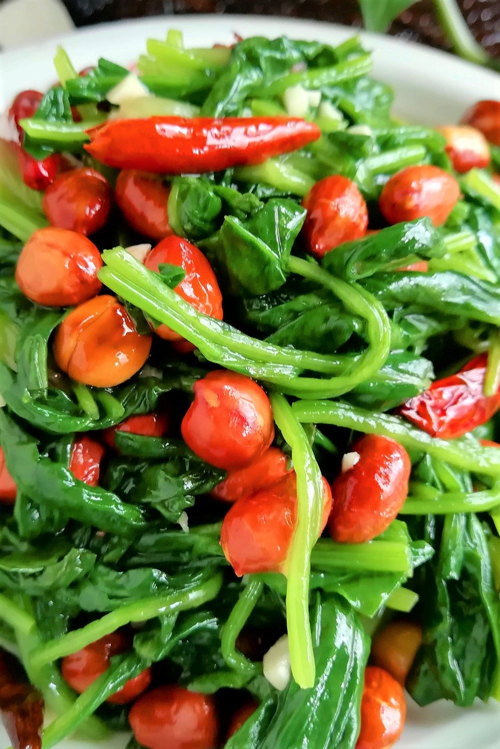 Ingredients:  500 grams of spinach, 1 small bowl of peanuts, moderate oil and salt, 1 tablespoon of sesame oil, 2 cloves of garlic, 10 dried chili peppers, 1 tablespoon of light soy sauce, half a tablespoon of sugar, 1 tablespoon of rice vinegar